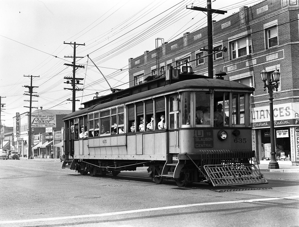 A trolley car filled with riders on a city street, with several storefronts visible in the background