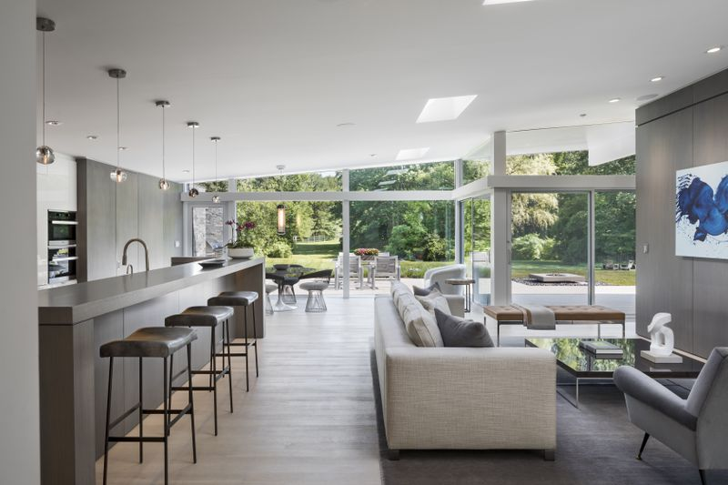 Open living area and kitchen with glass walls overlooking greenery.