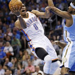 Oklahoma City Thunder guard Russell Westbrook (0) shoots in front of Denver Nuggets guard Ty Lawson, right, during the first quarter of an NBA basketball game in Oklahoma City, Wednesday, April 25, 2012.
