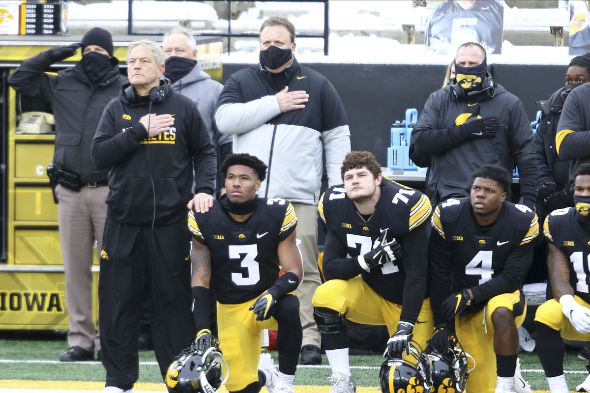 Head coach Kirk Ferentz of the Iowa Hawkeyes places his hand on the shoulder of wide receiver Tyrone Tracy #3 as he kneels during the anthem before the match-up against the Wisconsin Badgers at Kinnick Stadium on December 12, 2020 in Iowa City, Iowa.