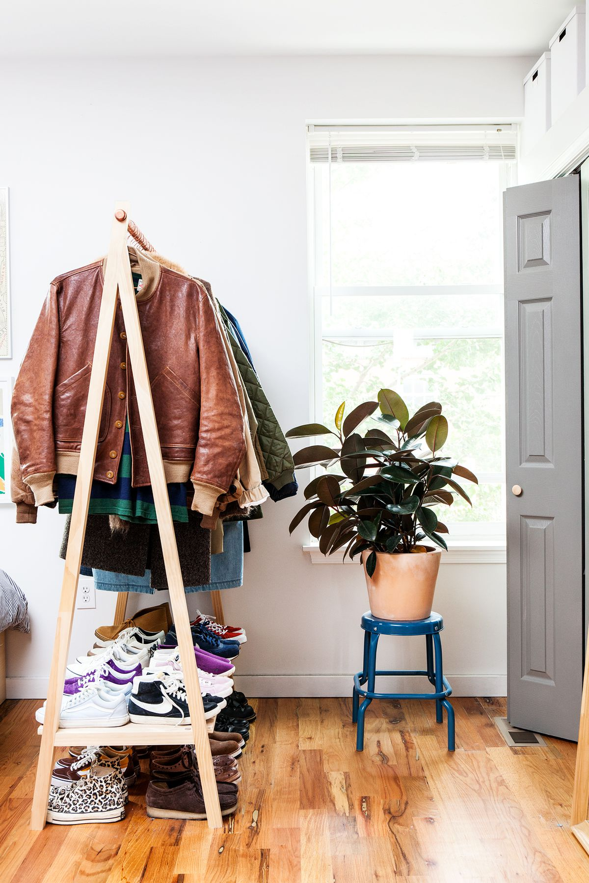 A wooden triangular clothes rack hangs by a window. A large plant sits on a blue stool nearby.