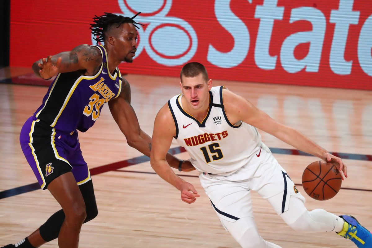 Denver Nuggets center Nikola Jokic (15) dribbles the ball against Los Angeles Lakers center Dwight Howard (39) during the third quarter in game five of the Western Conference Finals of the 2020 NBA Playoffs at AdventHealth Arena.