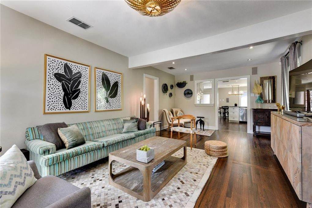 A narrow living room with a teal stiped sofa along one wall and a console with a TV on it across the room. Two black and white prints of leaves hang above the sofa.