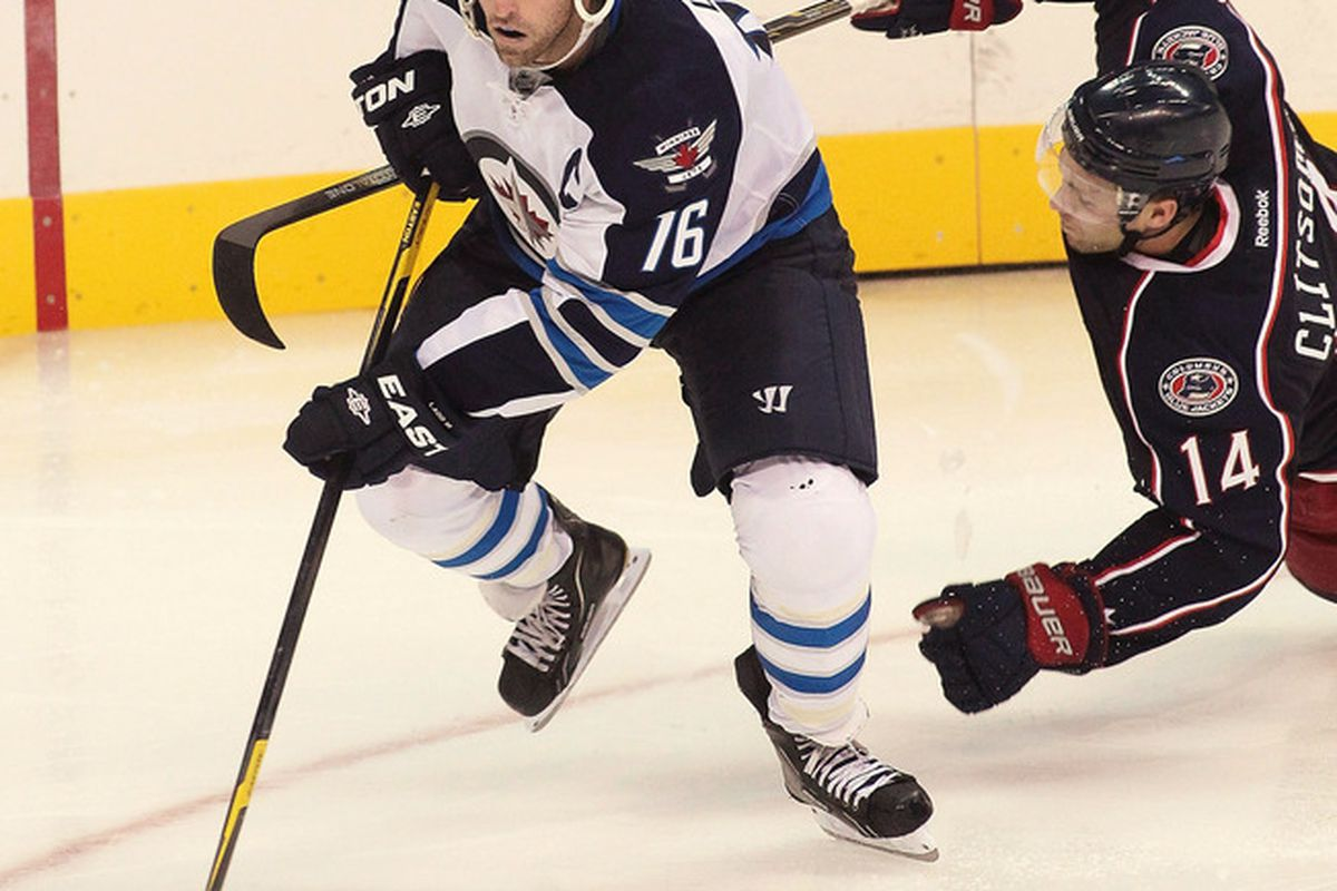 WINNIPEG, CANADA - SEPTEMBER 20: Andrew Ladd #16 of the Winnipeg Jets gets past Grant Clitsome #14 of the Columbus Blue Jackets at the MTS Centre on September 20, 2011 in Winnipeg, Manitoba, Canada. (Photo by Marianne Helm/Getty Images)
