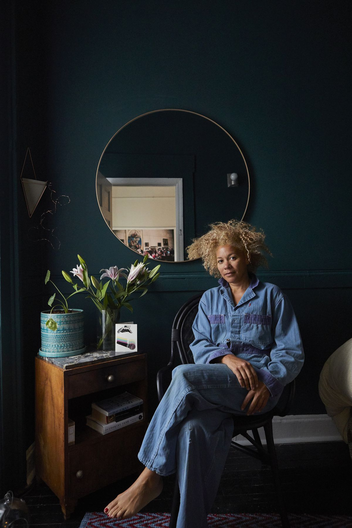 The photographer poses in room with deep blue-green walls. There is a mirror on the wall and a table with a vase of flowers on it.