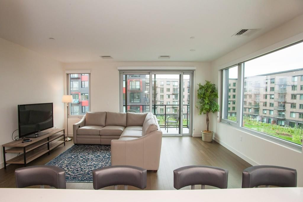 A long living room leading to a private terrace with a sectional couch.
