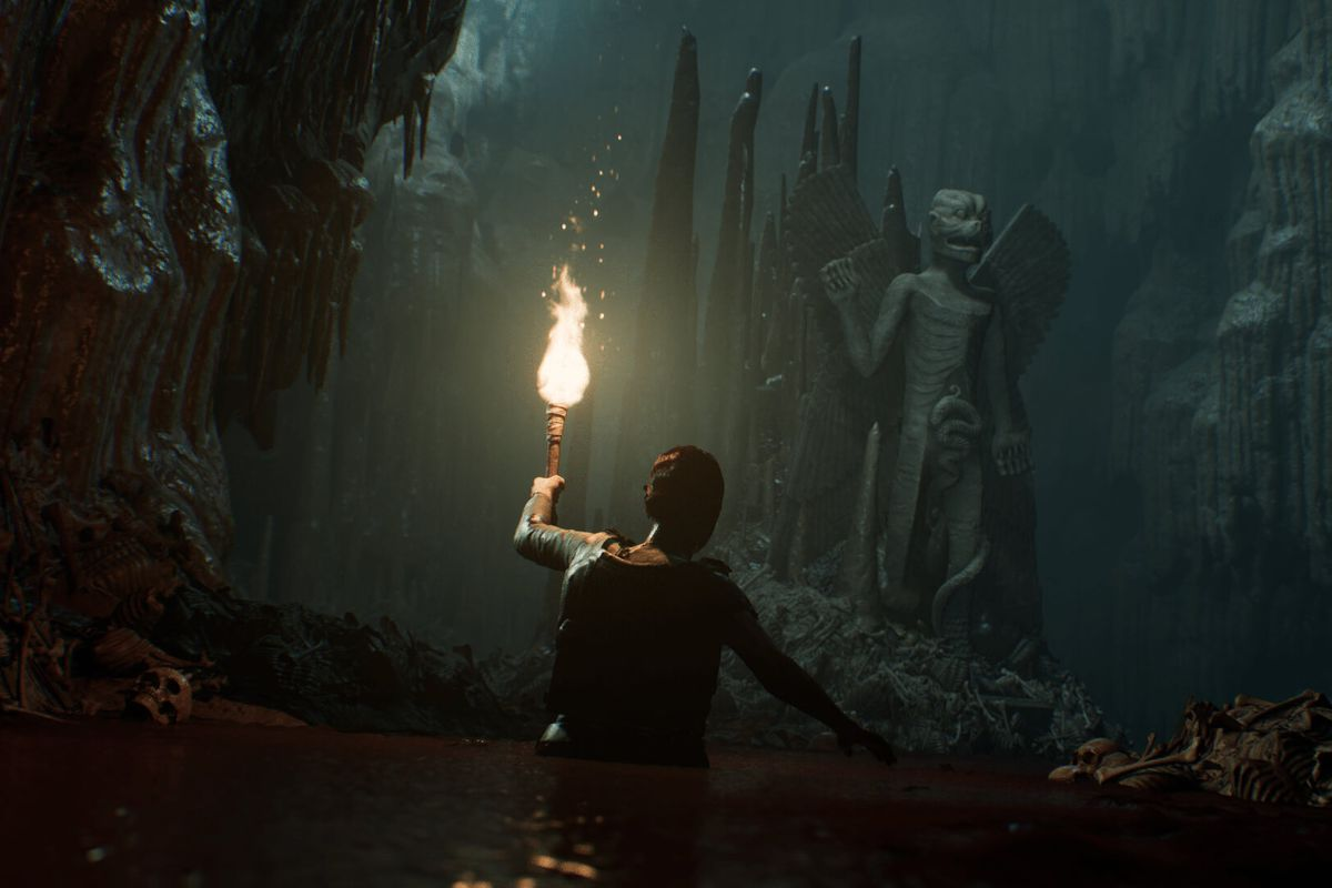House of Ashes - a person, holding a torch- wades through deep water as they approach a giant, sinister stone statue