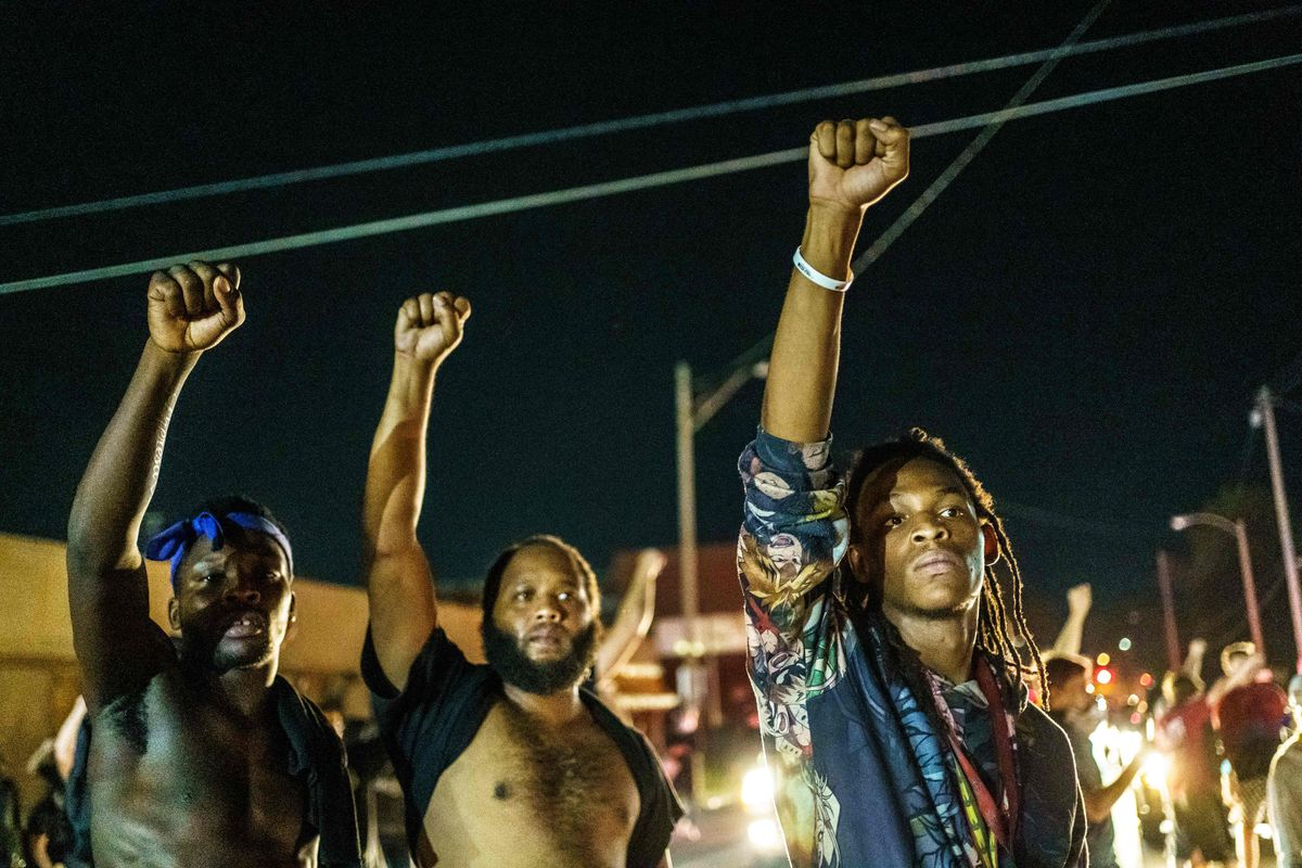 Three young black men, two of them shirtless, stand together, raising their right fists high into the air. The man on the right is wearing a multicolored shirt with the sleeves pushed up. They are lit by the yellow glow of sodium lights and by the lights of passing cars. A crowd of protesters is clustered behind them.