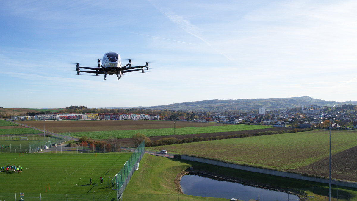 An EHang drone taxi above unknown landscape.