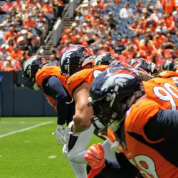 The defense warms up at the Broncos Training Camp practice at Broncos Stadium at Mile High.