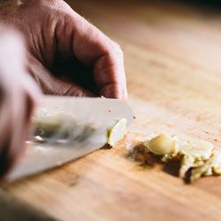 """The """"lonzino"""" is sliced thinly and piled atop the charcuterie board."""