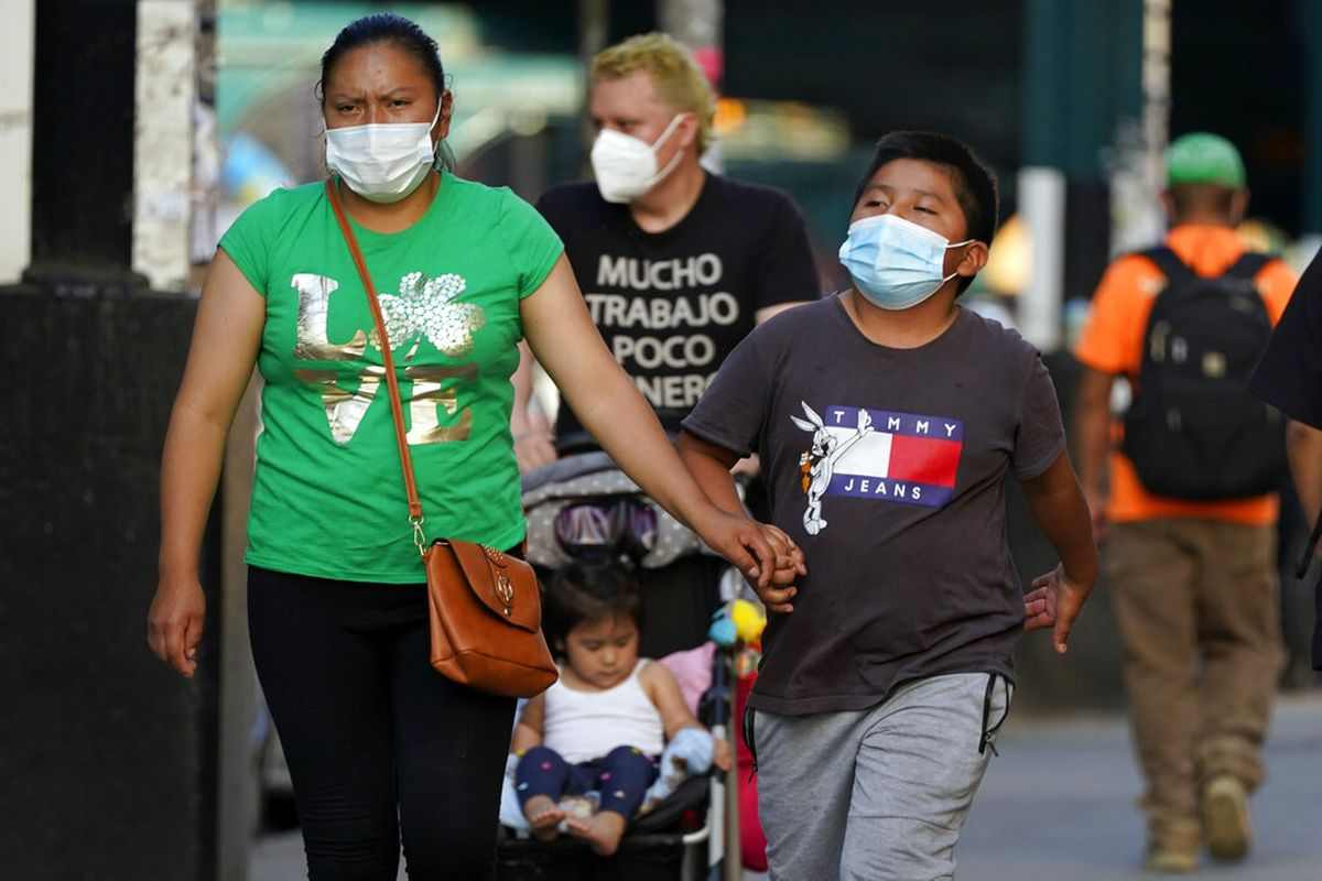 People wear protective masks during the coronavirus pandemic, in the Queens borough of New York.