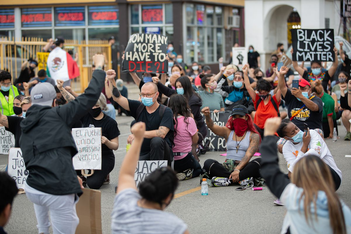 Protestors kneel and take a minute of silence in respect to George Floyd during a protest on 26th St. in Little Village, Chicago, Wednesday June 3, 2020. After days of radicalized violence in Little Village, community residents march to defend black lives and call out the mayor for defending downtown while turning her back on communities. (Anthony Vazquez/Sun-Times)