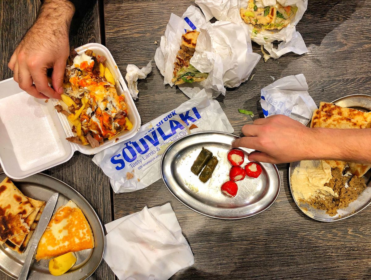 An overhead shot of a table with a styrofoam container of Greek fries and metal plates with flatbread, radishes, and grape leaves. Two hands reach in for the food.