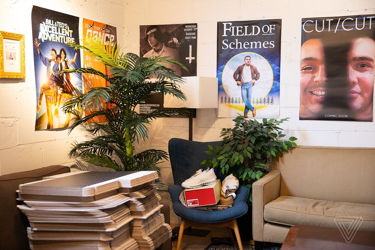 Couches and chairs are in crowded nook of a room with posters on the partitions, a pair of sneakers and other things in a pile.