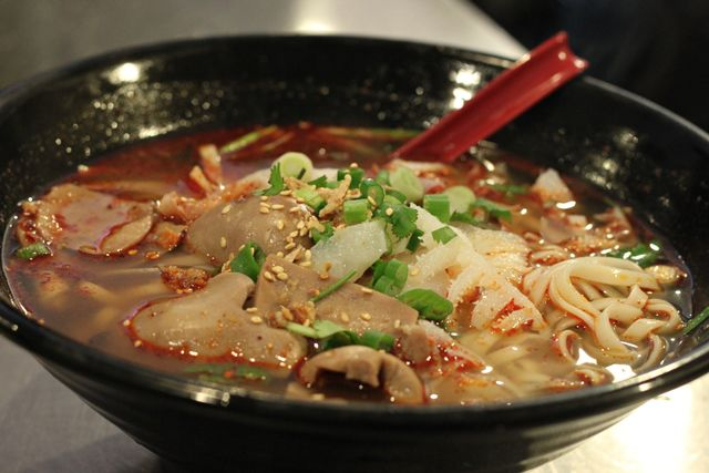 A bowl of noodles with broth and meat.