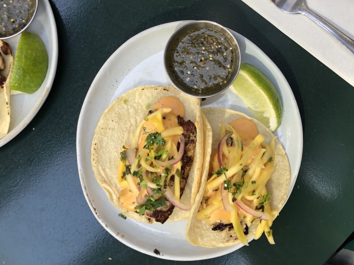 A white plate with some tacos on it that have fish and an orange sauce and some thin slices of mango