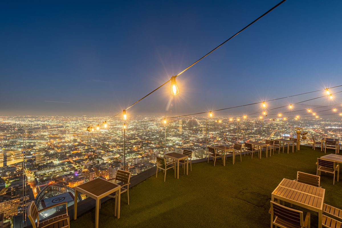 String lights and the glow of a city from a very tall open air patio.
