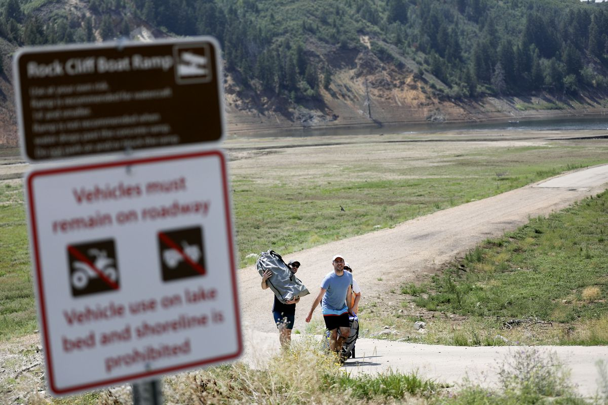 The Dobben family, who is visiting from Illinois, makes the walk back to their car after kayaking at Jordanelle State Park near Kamas on Wednesday, Aug. 4, 2021. The Rock Cliff boat ramp remains out of the water but smaller vessels may be launched off the old road at the bottom of the ramp.