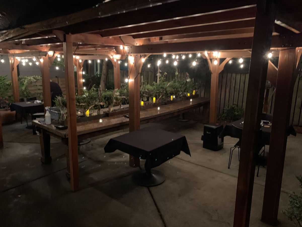 A covered patio with wood tables, strings of white Christmas lights and landing tables between the booths