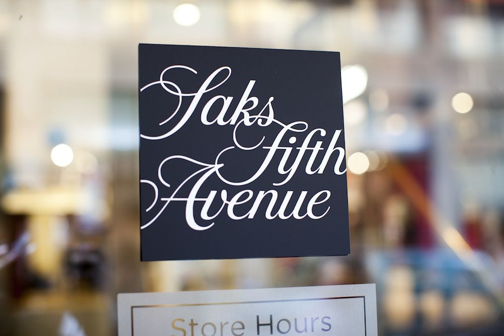 A Saks Fifth Avenue store sign on glass.