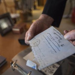 Eighty-seven-year-old retired Marine John Cole, who served and was wounded in North Korea, looks through old war documents at his home in Roy Wednesday, Feb. 18, 2015.