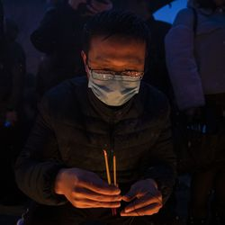 A man lights incense as hundreds gather for a vigil in a parking lot in the 2000 block of South Wells in Chinatown, where Huayi Bian and Weizhong Xiong were shot to death, Wednesday, Feb. 12, 2020. Bian and Xiong were killed during an apparent robbery, for which Alvin Thomas faces two counts of first-degree murder.