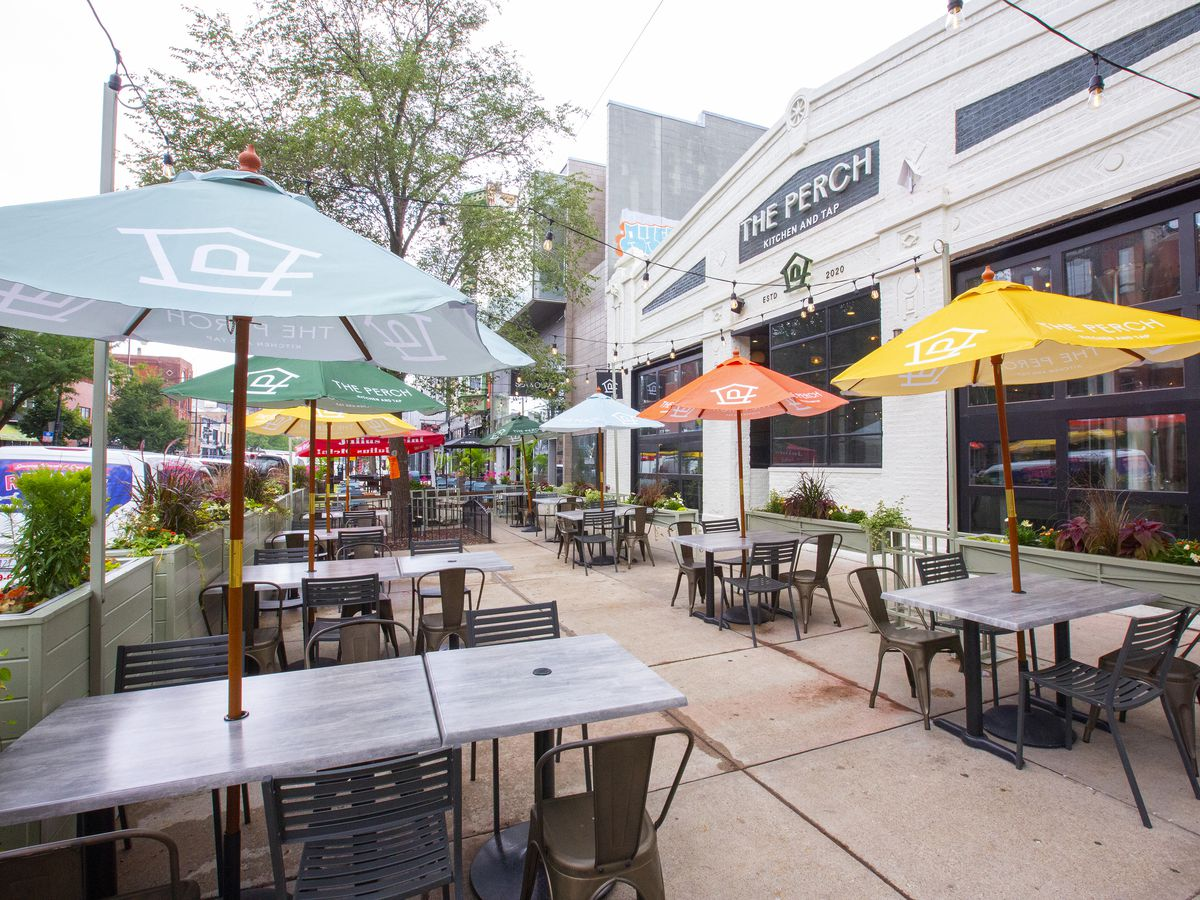 Sidewalk patio seating in front of a restaurant with square tables and large, colorful umbrellas.