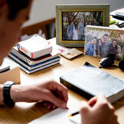 Family photos adorn the desk of Elder Tanner McKee, a missionary for The Church of Jesus Christ of Latter-day Saints, as he studies at the home he shares with three other missionaries in Paranaguá, Brazil, on Saturday, June 1, 2019.