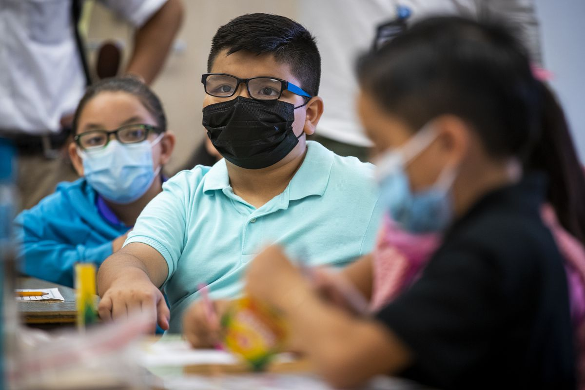 Children wearing masks sit at a classroom table.