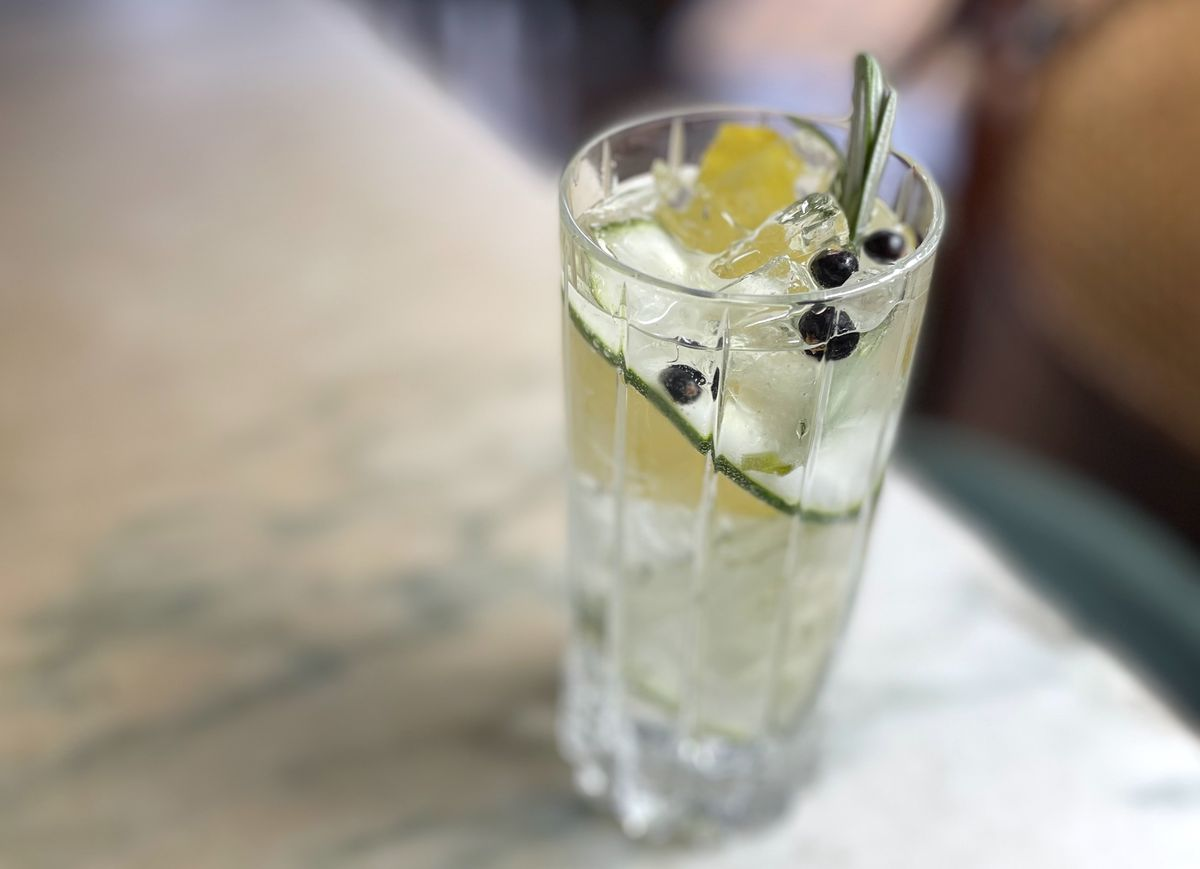 A highball glass is filled with a clear liquid, garnished with a cucumber ribbon, lemon zest and a few juniper berries. The glass sits on a marble topped table. The historic wood filled interior of Frost's bar is barely visible in the background.