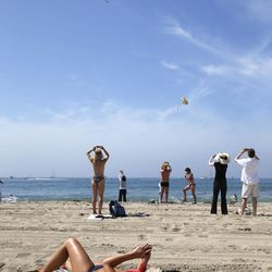 Spectators take pictures as the Space Shuttle Endeavour mounted on NASA's Shuttle Carrier Aircraft (SCA) flies near Santa Monica, Calif., Friday, Sept. 21, 2012.