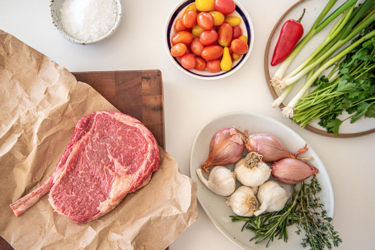 Tomahawk ribeye steak with onions, tomatoes, and herbs from Blue Box Butcher