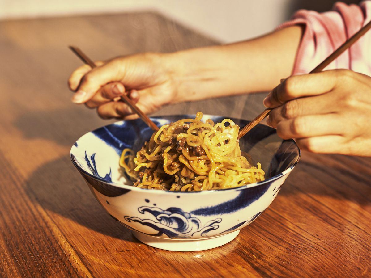 Ramen noodles in a blue and white ceramic bowl with a person lifting the noodles with chopsticks.
