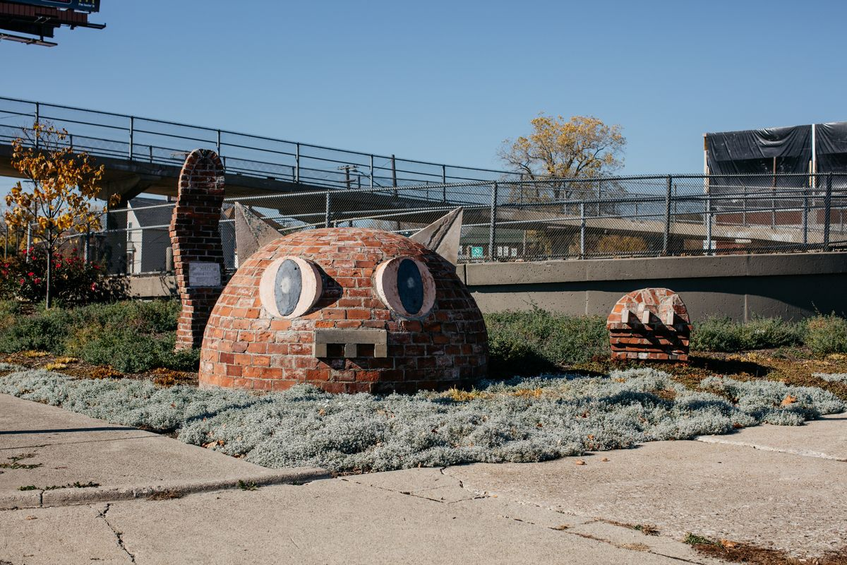 An outdoor sculpture of a cat which is crafted out of many red bricks. The cat's head is rising out of the ground.