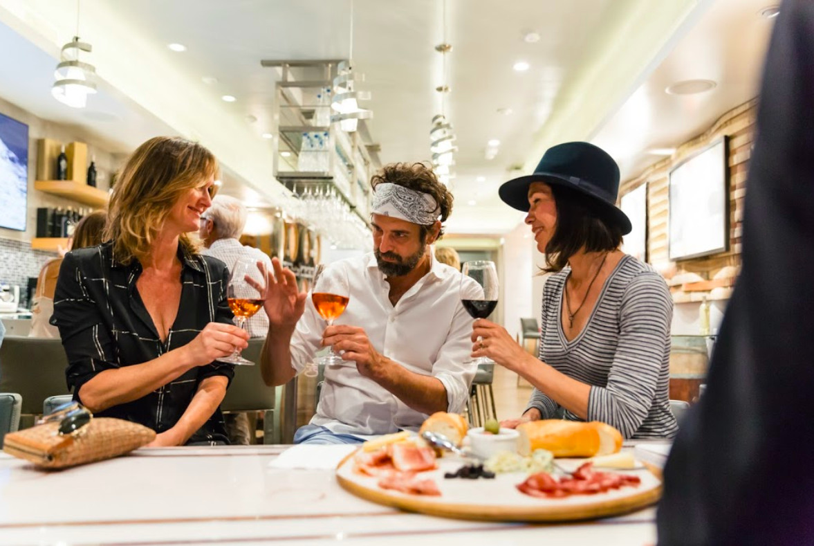 A man and two women tasting wine and a charcuterie plate.
