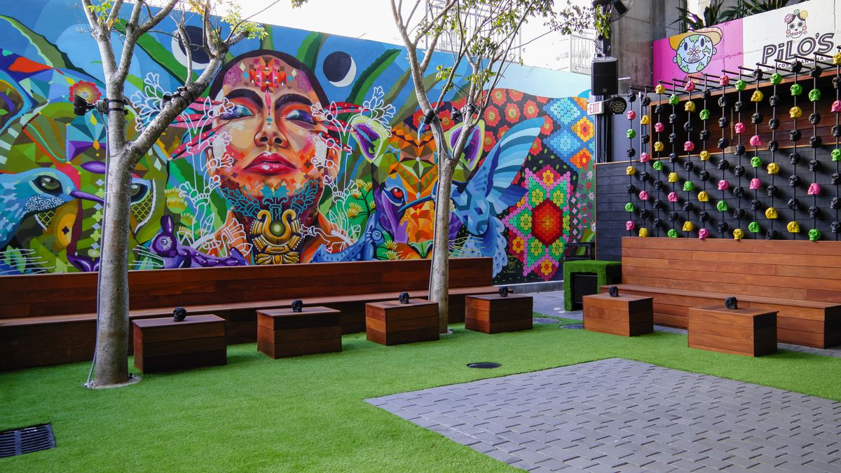 Colorful patio with green grass, large mural, bar with mannequin heads