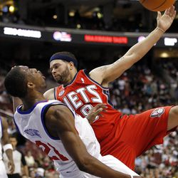 Philadelphia 76ers forward Thaddeus Young (21) draws the charging foul as he is hit by New Jersey Nets guard Deron Williams (8) in the first half of an NBA basketball game on Friday, April 13, 2012, in Philadelphia. (AP Photo/Alex Brandon)