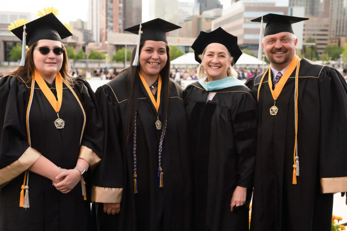Brooke Waring, left, NaTasha Montoya, and James Osborn are the first graduates of a University of Colorado Denver partnership with Otero Junior College. At commencement, they posed with Associate Dean Barbara Seidl.