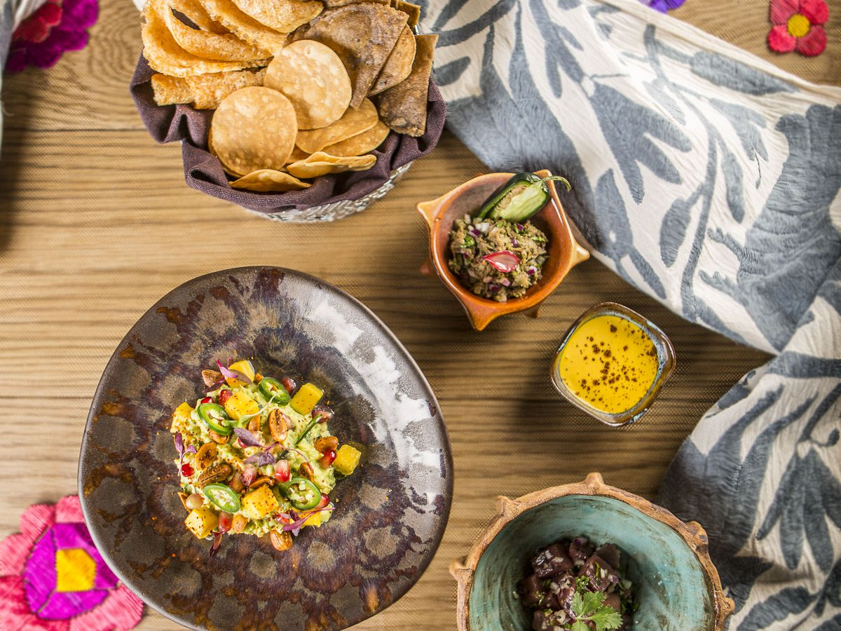 A top-down view of various dishes involved in the table-side guacamole presentation at Punto MX