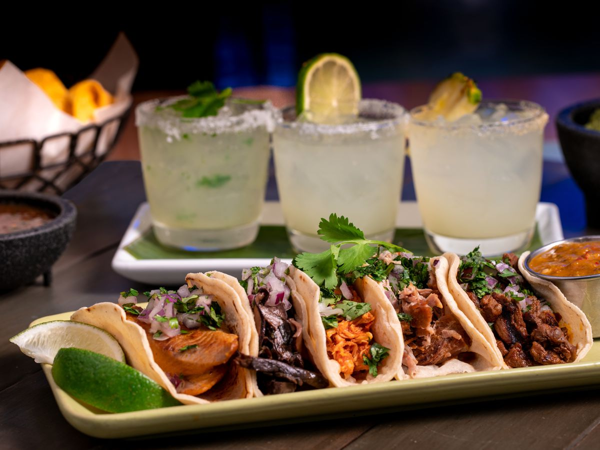 A plate of tacos with margaritas in the background at Cañonita in Las Vegas.