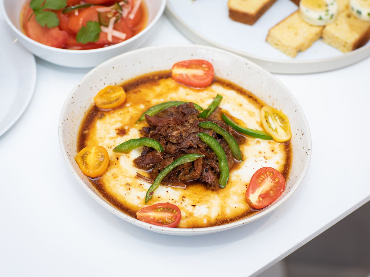 A white bowl with yellow-ish grits, pieces of tomato, some brownish meat on top, and slices of peppers
