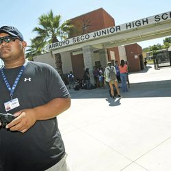 Campus supervisor Jerome Castaneda monitors the parking lot following dismissal at Arroyo Seco Junior High School in the Valencia neighborhood of Santa Clarita, Calif., Tuesday, Sept. 18, 2012.  Eric Yee, accused of posting comments on ESPN's website saying he was watching kids and wouldn't mind killing them, was in jail Tuesday on $1 million bail after he was arrested at his home near the school for investigation of making terrorist threats, authorities said.