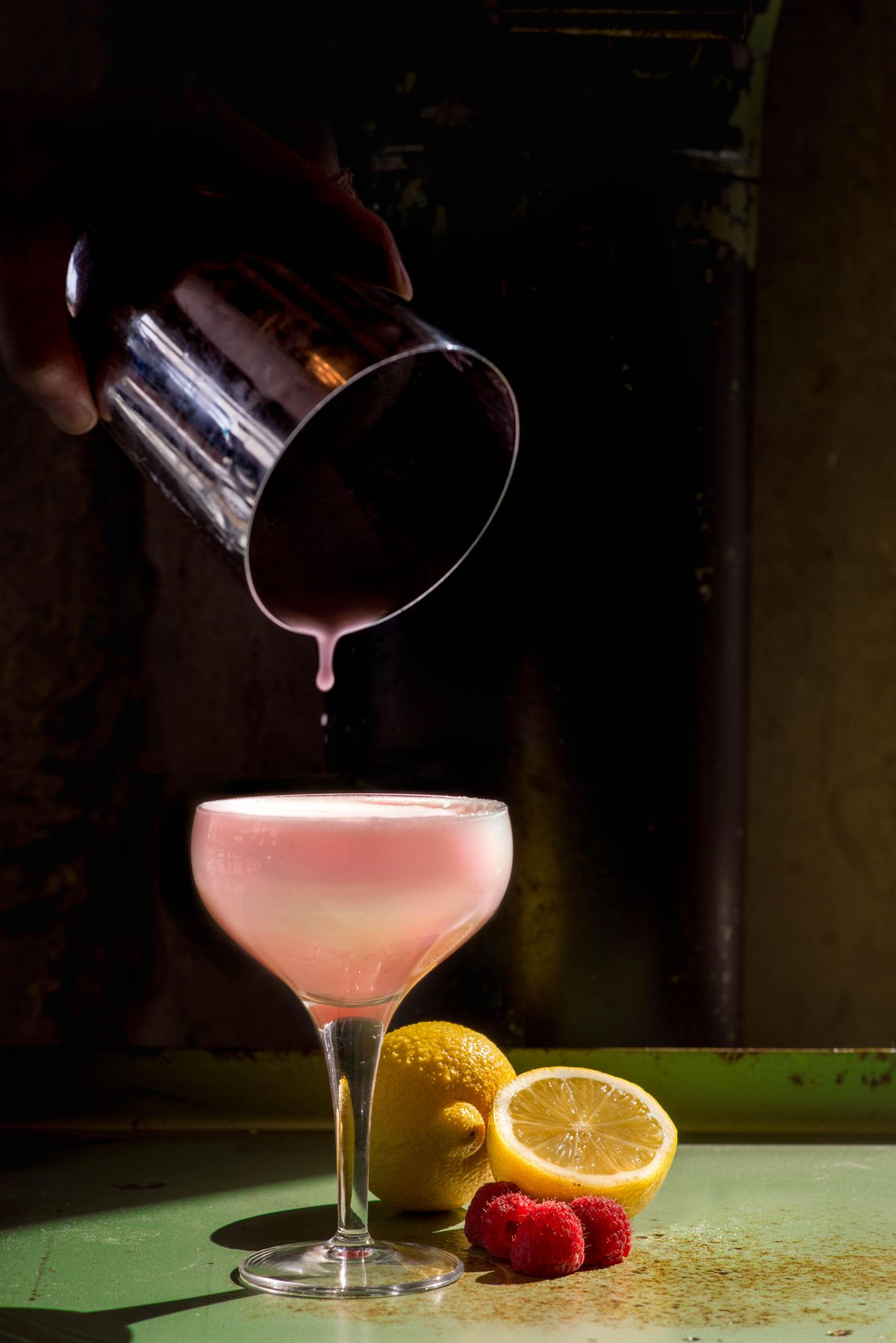 A hand pouring the pink-colored Witless Lion zero-proof cocktail into a coupe glass from a tin shaker at Biltong Bar in Atlanta, GA