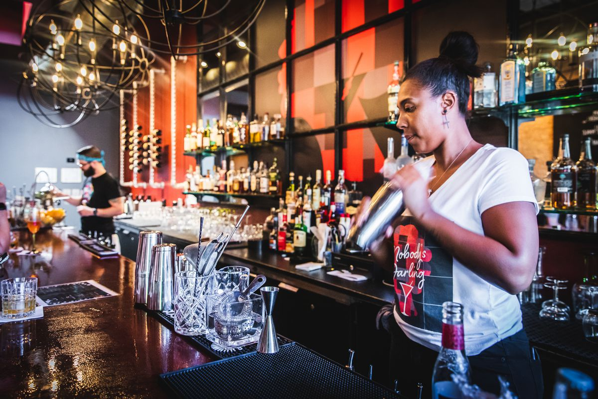 A bartender holds a metal cocktail shaker inside a black-and-red bar space