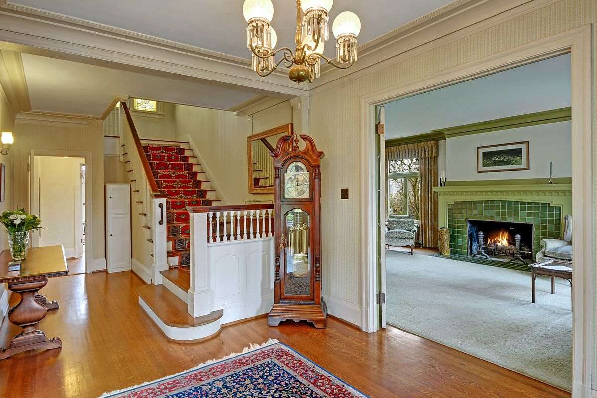 A foyer with hardwood floors leads to a large staircase. A large doorway with French doors leads to a living room with a green fireplace.