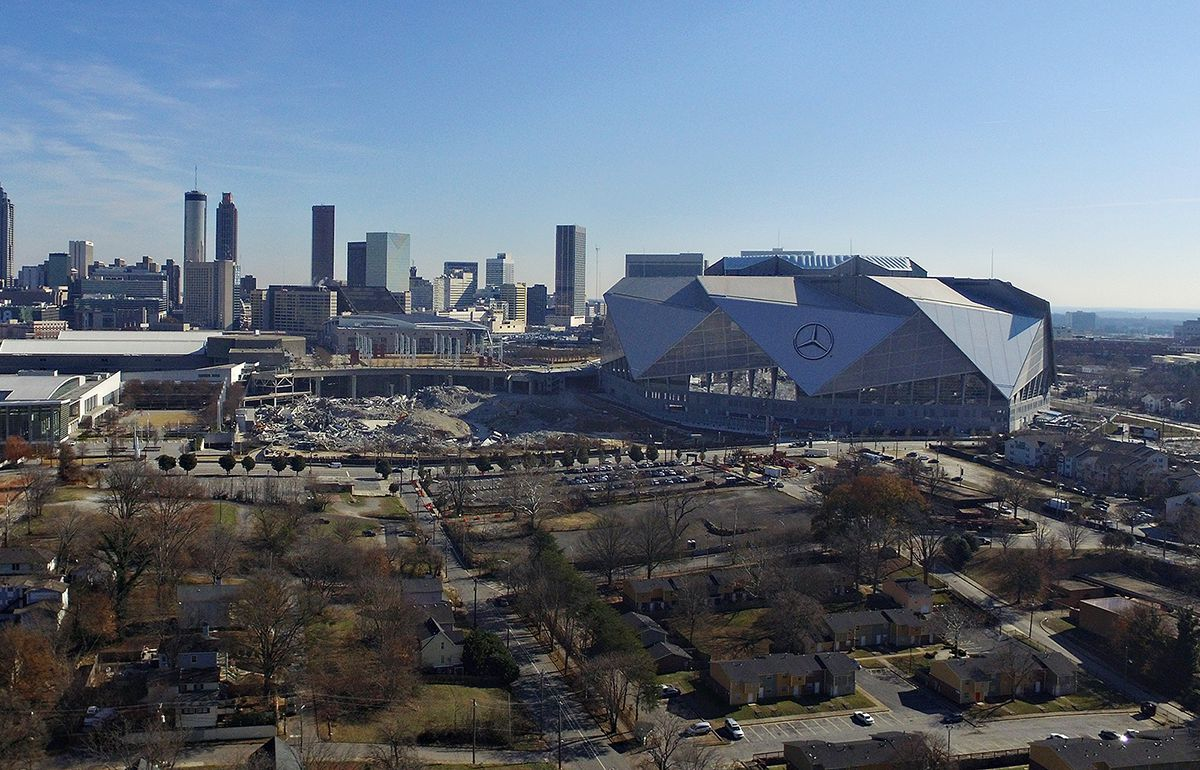 A massive gray stadium with rubble beside it, and a skyline beyond.