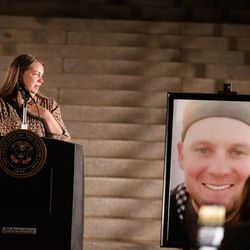 Nancy, cousin of Staff Sgt. Taylor Hoover, looks at his portrait while speaking during a vigil to honor his life and serviceat the Capitol in Salt Lake City on Sunday, Aug. 29, 2021. Hoover was one of the 13 U.S. service members killed by the terrorist attack at Hamid Karzai International Airport in Kabul, Afghanistan.