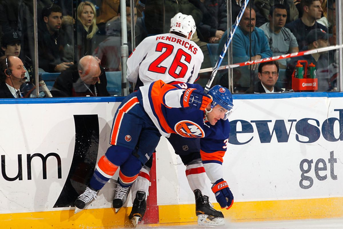 UNIONDALE NY - JANUARY 20:  Matt Hendricks #26 of the Washington Capitals checks Jack Hillen #38 of the New York Islanders on January 20 2011 at Nassau Coliseum in Uniondale New York.  (Photo by Lou Capozzola/Getty Images)