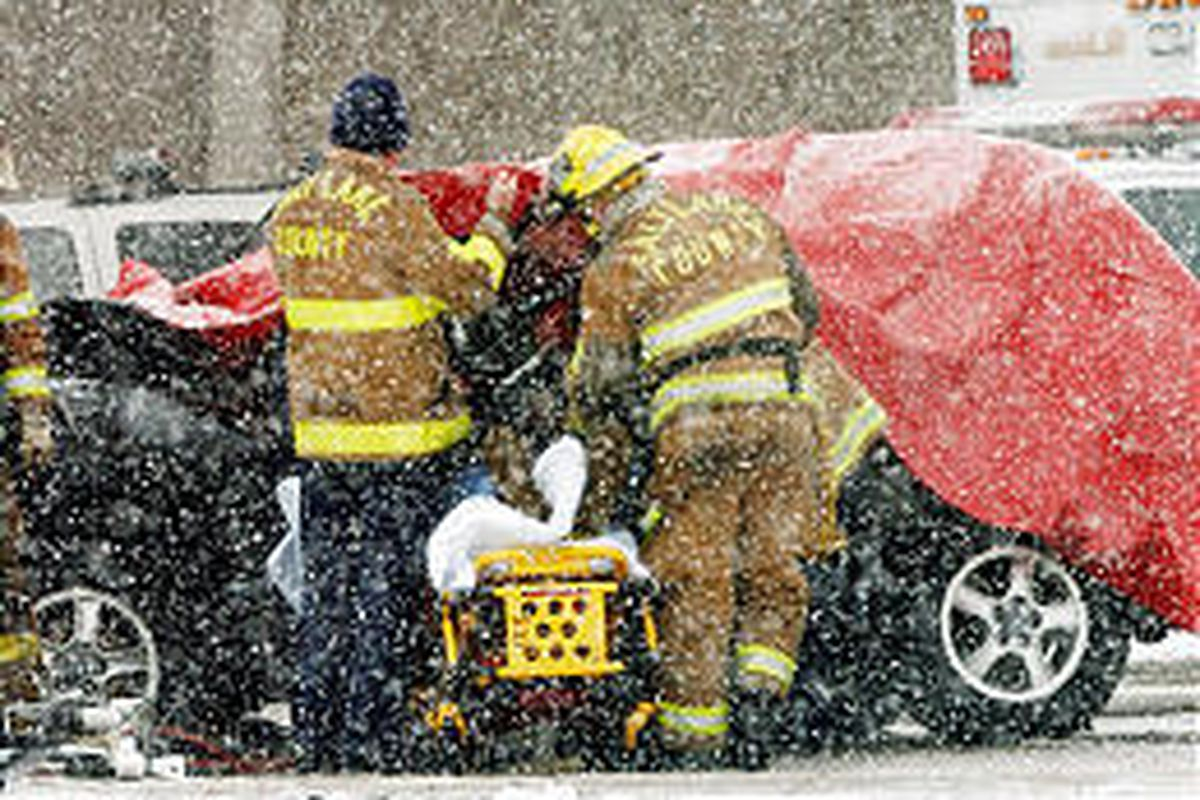 Salt Lake County emergency crews work to remove the victims of the crash on I-215, near 3500 South.